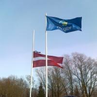 Latvijas karogs sēru noformējumā šodien uz Rīgas robežas. Kas šajā attēlā ir ačgārns?